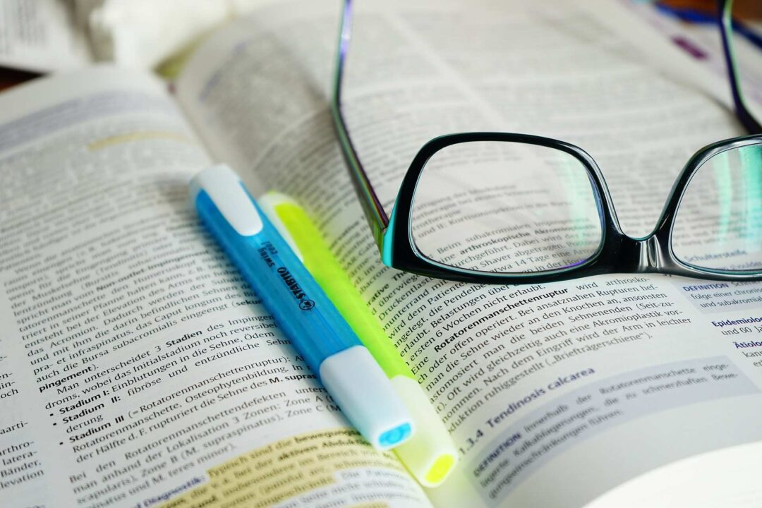 Buch mit Brille und Stift